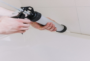 person caulking along a bathrub