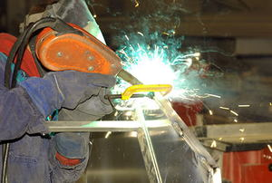 A worker in a fabrication shop welding aluminum.