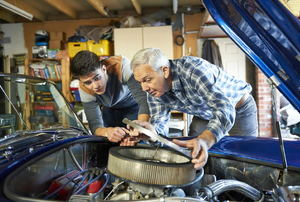 A father and son working on a classic car together.
