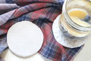 A pair of clay coasters with a drink on top and a flannel tablecloth.