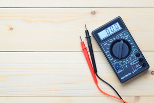 A black multimeter with a red and black probe lays on a wood surface.