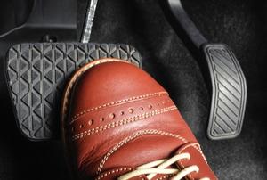 foot in shoe pressing brake pedal