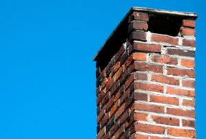 A worn, brick chimney against a blue sky.