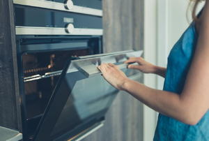 A woman opens an oven door.