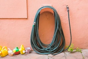 A garden hose on the side of a house.