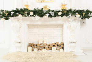 A white fireplace and mantle with Christmas decor including a garland and candles.