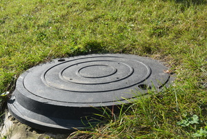 A septic tank cover in the ground.