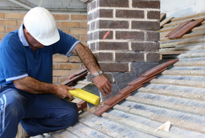 Man working on a roof near a chimney