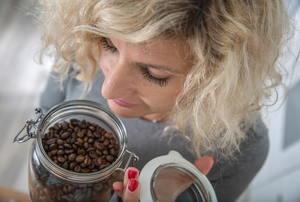 A woman smelling a jar of coffee beans.