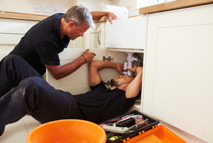 Two men working on plumbing under a kitchen sink