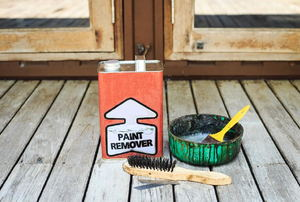 A can of paint remover on a wood deck.
