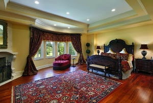 A luxurious bedroom featuring a large, Persian rug and a bay window.