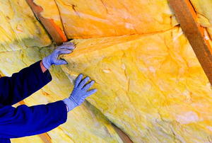 Hands installing a fiberglass batts in the rafters of an attic.