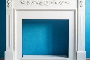 empty fireplace frame in front of blue wall