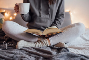 A woman sitting on a bed in sweat pants and a hoodie, holding a coffee mug and a book.