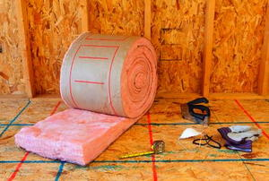 A roll of insulation and some tools in an unfinished room.