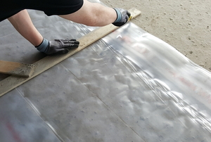 hands cutting plastic sheeting along a wooden frame