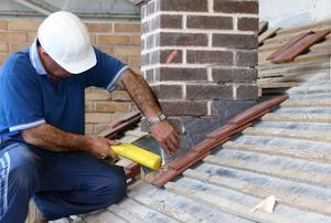 Man installing flashing around a chimney