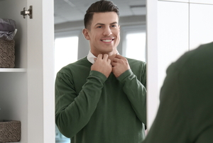 man getting dressed with closet door mirror