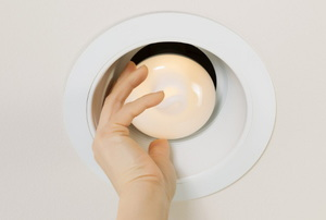 A recessed light with a hand adjusting the bulb.