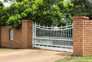 A white metal gate across a driveway.