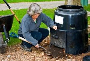 A woman collects fresh compost from a composter.