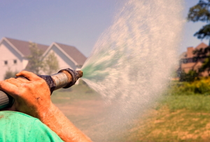 person spraying hydroseed mixture from hose