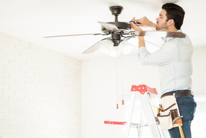a man fixing a ceiling fan