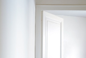 A white interior door sits ajar at the end of a hall.