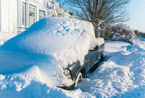 truck buried in deep snow next to a house