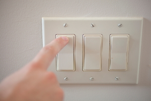 A hand turning on a panel light switch.