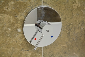 A chrome shower fixture attached to a granite wall.