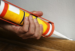 Using a caulking gun, sealant is applied along the edge of a piece of baseboard trim.