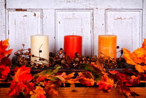 Three candles of white, red, and yellow on a mantlepiece surrounded by fall berries and leaves.