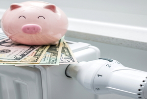 A piggy bank sitting on top of a stack of cash on a heater.