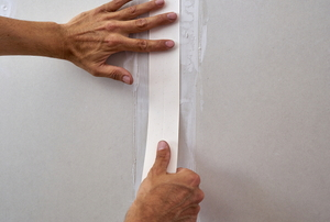 hands applying drywall tape to seal