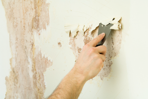 A man removes wallpaper.