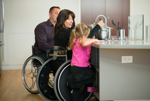 A couple in wheelchairs cooks in an accessible kitchen with their daughter.