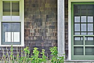 wood storm door in front of building with wooden shingles