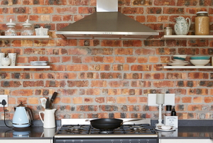 A brick walled kitchen with shelves