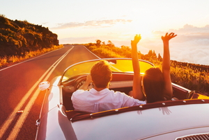 A couple driving in a convertible on a sunny road