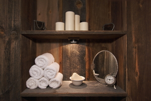 A rustic bathroom with rolled towels and candles.