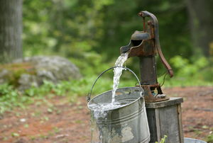 a hand pump outdoor water spout pouring water into a bucket