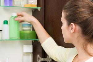 woman opening bathroom cabinet