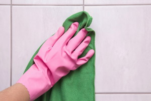 A pink gloved hand holding a green cloth against a shower wall.
