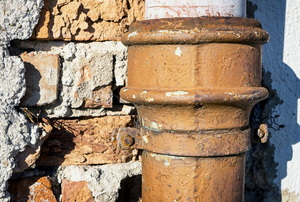 A rusty pipe against a brick wall.