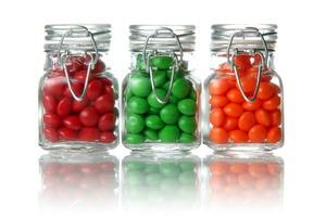 Three mason jars full of multi-colored candy.