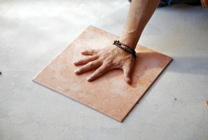 A man lays down porcelain tile flooring.