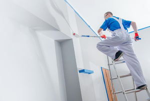 A man paints a room and ceiling white.