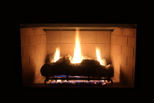 A propane-fueled fireplace burning in a dark room.